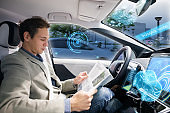 Caucasian driver reading magazine in autonomous car. Self driving vehicle.
