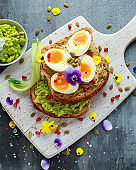 Tasty sandwich with avocado boiled eggs, pumpkin seed and edible viola flowers in a white board. healthy food
