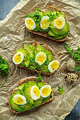 Healthy Avocado and quail eggs toasts with wild rocket and sea salt