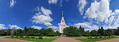 Wide angle frontal panoramic landscape view of light clouds over the sunny summer campus of Lomonosov Moscow State University under blue sky