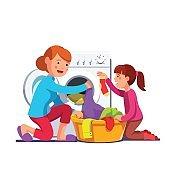 Girl help mum loading laundry to washing machine