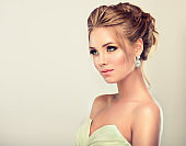 Young and attractive blond model dressed in evening gown and jewelry earings.