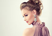 Young gorgeous girl dressed in evening gown and delicate makeup on.