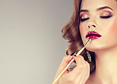 Hand of make-up master, painting lips of young beautiful model.