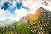 Sun flare bursting behind a mountain peak