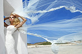 Beautiful bride blonde female model in amazing wedding dress poses on the island of Santorini in Greece and beyond it is a beautiful view