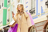 Stylish, beautiful blonde hair smiling girl with shoppings using her phone. Happy shopping.