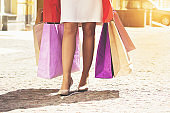 Happy shopping concept. Closeup portrait of fashionable girl in red coat walking with shopping bags. Mall sale concept.