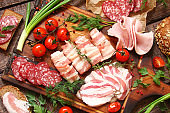 Delicatessen, smoked meat, bacon, vegetables, tomatoes, parsley on a wooden boards