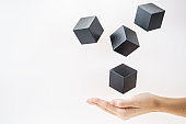 Black wooden cubes are floating on open woman hand.  Concept of creative, logical thinking. Abstract background with cubes with copy space. Shape floating.