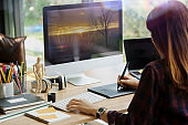 Young hipster graphic designer woman using digital graphic tablet while working at modern office, professional female retoucher sitting at modern workspace with wooden table