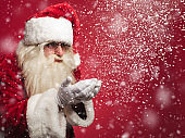 santa claus is blowing snow flakes out of his palms
