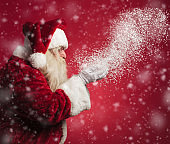 side view of santa claus blowing snow from his hands