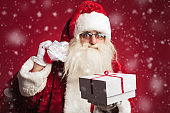 santa claus holding bag on shoulder and offering  present