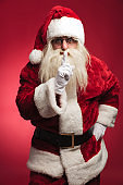 surprised santa claus making silence sign