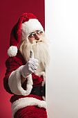 santa claus sitting near  blank board and makes ok sign