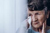 Sad elderly woman wiping tears