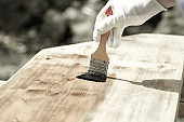 Painter painting wooden surface, protecting wood