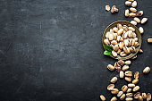 Pistachio nuts on dark background, top view, healthy snack