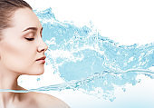 Sensual woman in wave splashes of clear water.