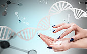 Female hands with cream over dna and molecules.