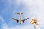 Woman with airplane flying on the background