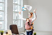Businesswoman with her baby son working with documents at the office