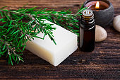 Rosemary soap and essential oil aromatherapy with candle on wooden background