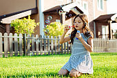 Adorable girl blowing soap bubbles near house