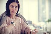 Unhappy ill woman having high body temperature