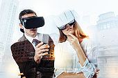Two elegant colleagues observing incredible virtual reality