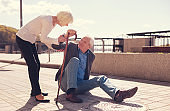 Caring woman offering help to a fallen man