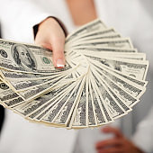 Woman banker in white with pack of dollars
