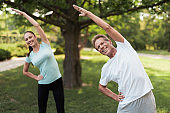 Man and woman doing exercises in the park. They warm up. They make slopes