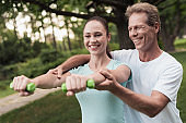 Girl doing exercises with dumbbells in the park. A man helps her. They are smiling