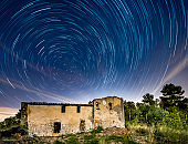 circumpolar startrails over abandoned house