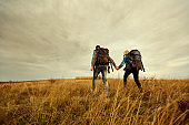 A young couple is traveling with backpacks across the field.