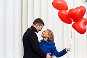 A loving couple in a coat with red ballons hearts in hands.