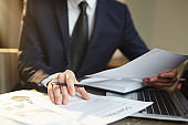 Closeup portrait of unrecognizable successful businessman wearing black formal suit reviewing finance statistics and contract documents at desk