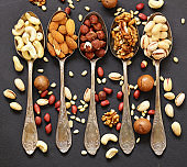 various kinds of nuts (cedar, cashew, hazelnuts, walnuts) in spoons