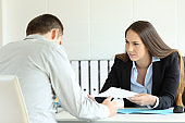 Angry boss giving document to a sad employee