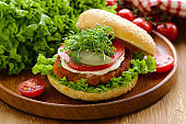 fresh homemade hamburger with vegetables and salad on a wooden table
