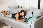 Happy young blonde man lying down in the couch at home on the computer 'n
