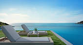 Sea view swimming pool beside terrace and beds in modern luxury beach house with blue sky background, Lounge chairs on green grass at vacation home or hotel