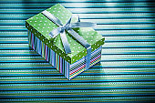 Wrapped present box on striped background holidays concept