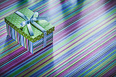 Cardboard present box with ribbon on striped tablecloth celebrat