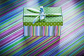Wrapped cardboard box with present on striped tablecloth celebra