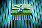 Wrapped gift box on striped background holidays concept