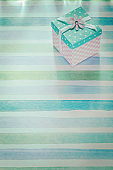 Wrapped gift box on blue striped fabric holidays concept