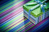 Wrapped cardboard box with gift on striped tablecloth celebratio